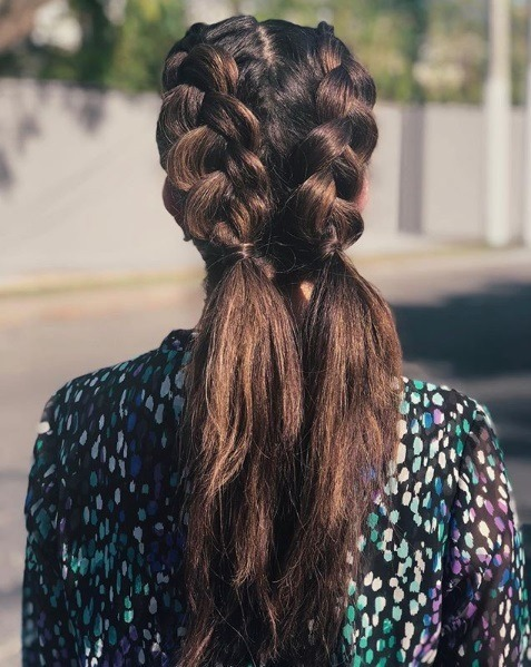 Back view of a brunette with long hair in double Dutch ponytail braids