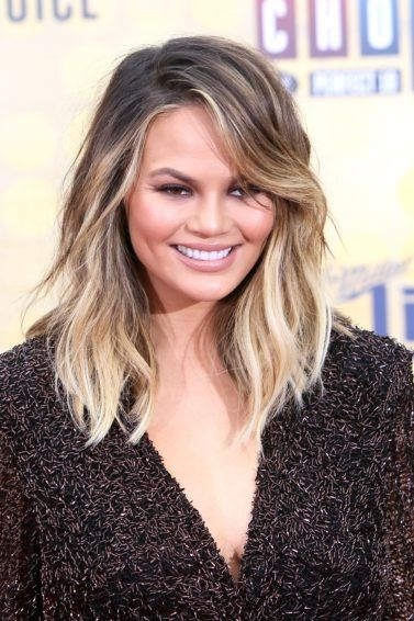 chrissy teigen on the red carpet with her hair in a brown to blonde balayage colour styled into loose waves