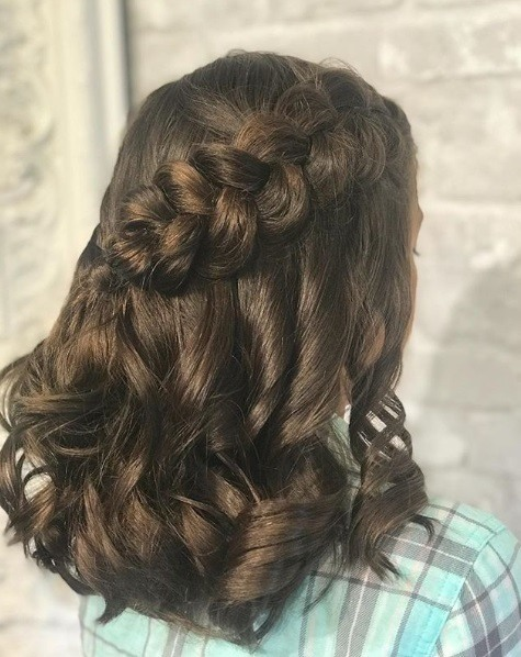 Close up shot of a brunette with curled shoulder length hair in a diagonal half-up half-down Dutch braid