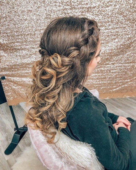 Woman with brown ombre hair sitting in a salon chair with a curly half-up half-down Dutch crown braid