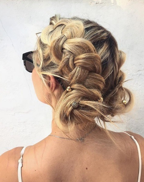 Blonde woman with Dutch braided buns wearing sunglasses