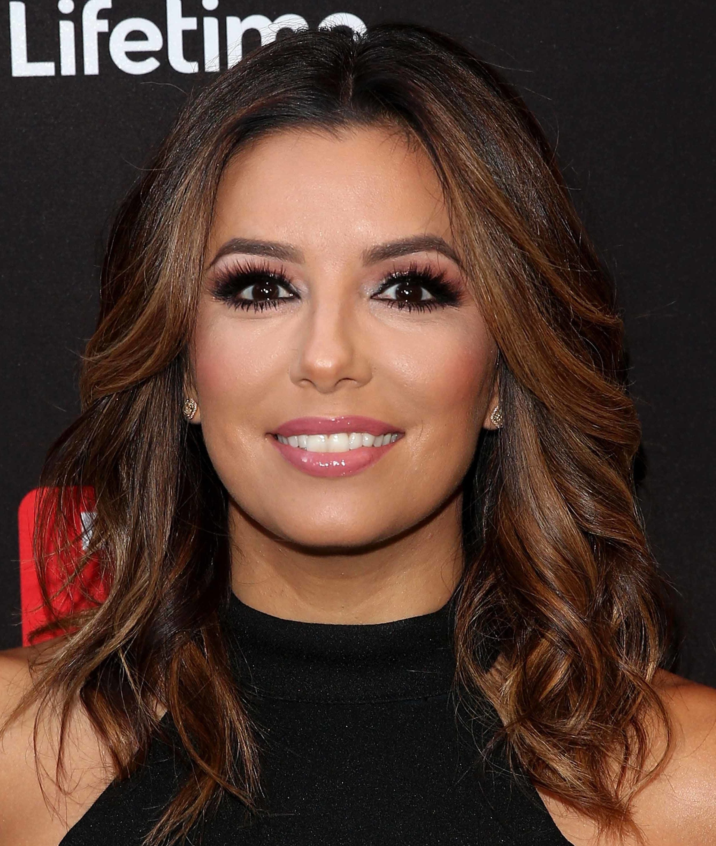 Eva Longoria with face framing caramel balayage medium length wavy hair wearing black high neck dress