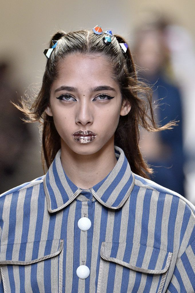 model on the Fendi SS17 runway with brunette hair worn in pigtails with candy look accessories attached and glitter lips wearing a striped outfit