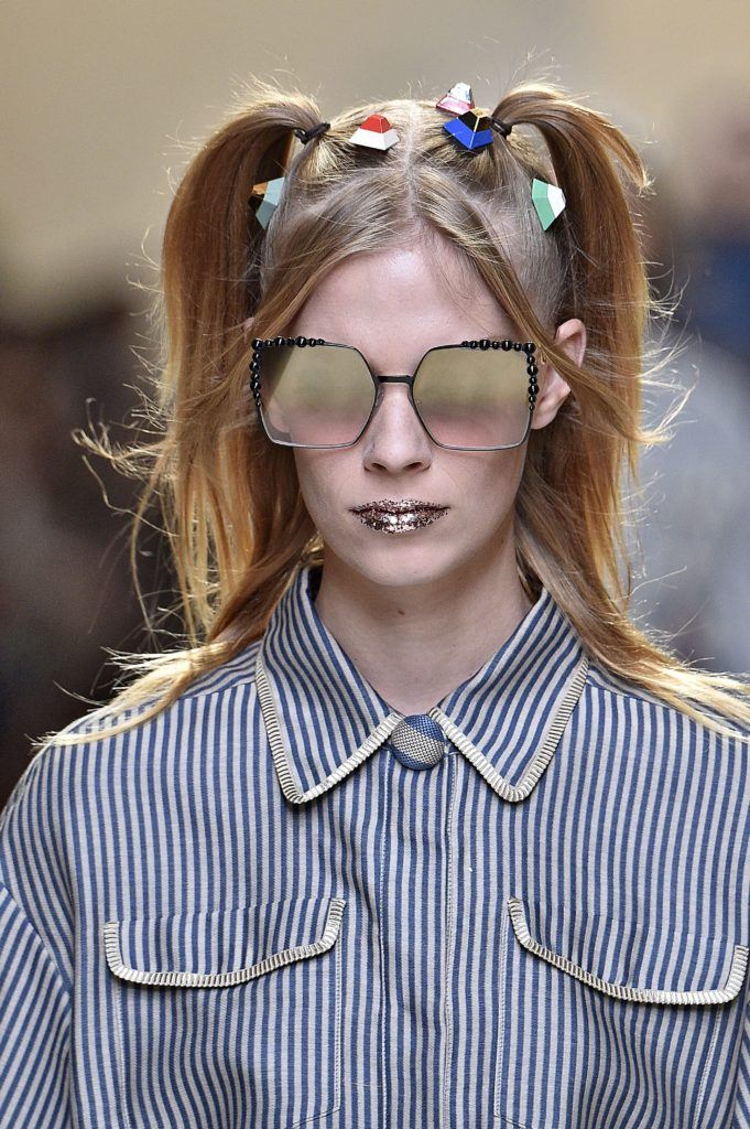 model on the Fendi SS17 runway with blonde hair worn in pigtails with candy look accessories attached and glitter lips wearing a striped outfit