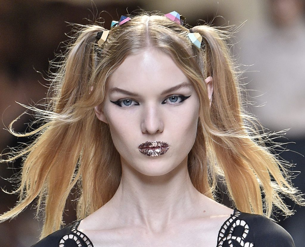 model on the Fendi SS17 runway with blonde hair worn in pigtails with candy look accessories attached and glitter lips