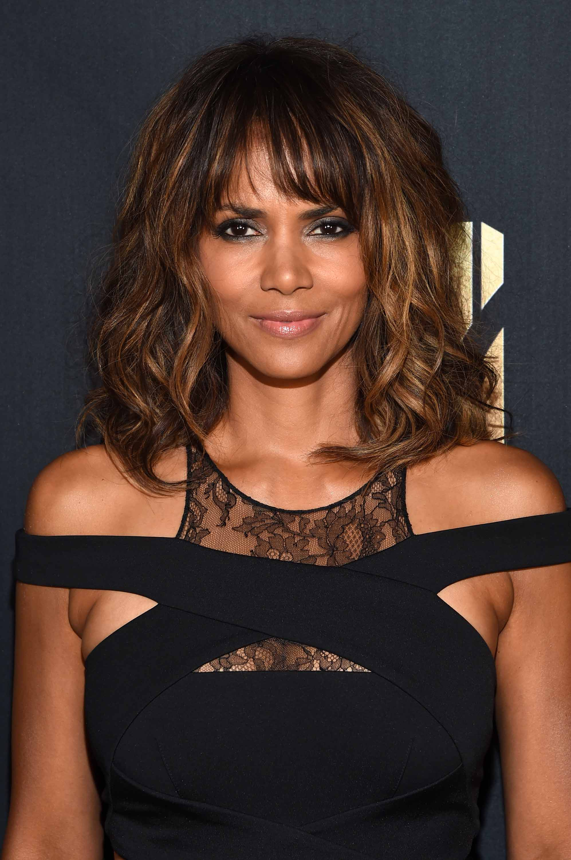 halle berry with caramel balayage brown shoulder length wavy hair and parted fringe wearing black lace detail dress