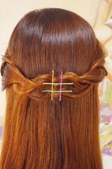 back view of a woman with copper hair styled straight and into a braid around her head held in place with 4 colourful bobby pins