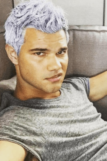 Taylor Lautner taking a selfie wearing a grey tshirt and khaki trousers with his dyed a lavender purple colour