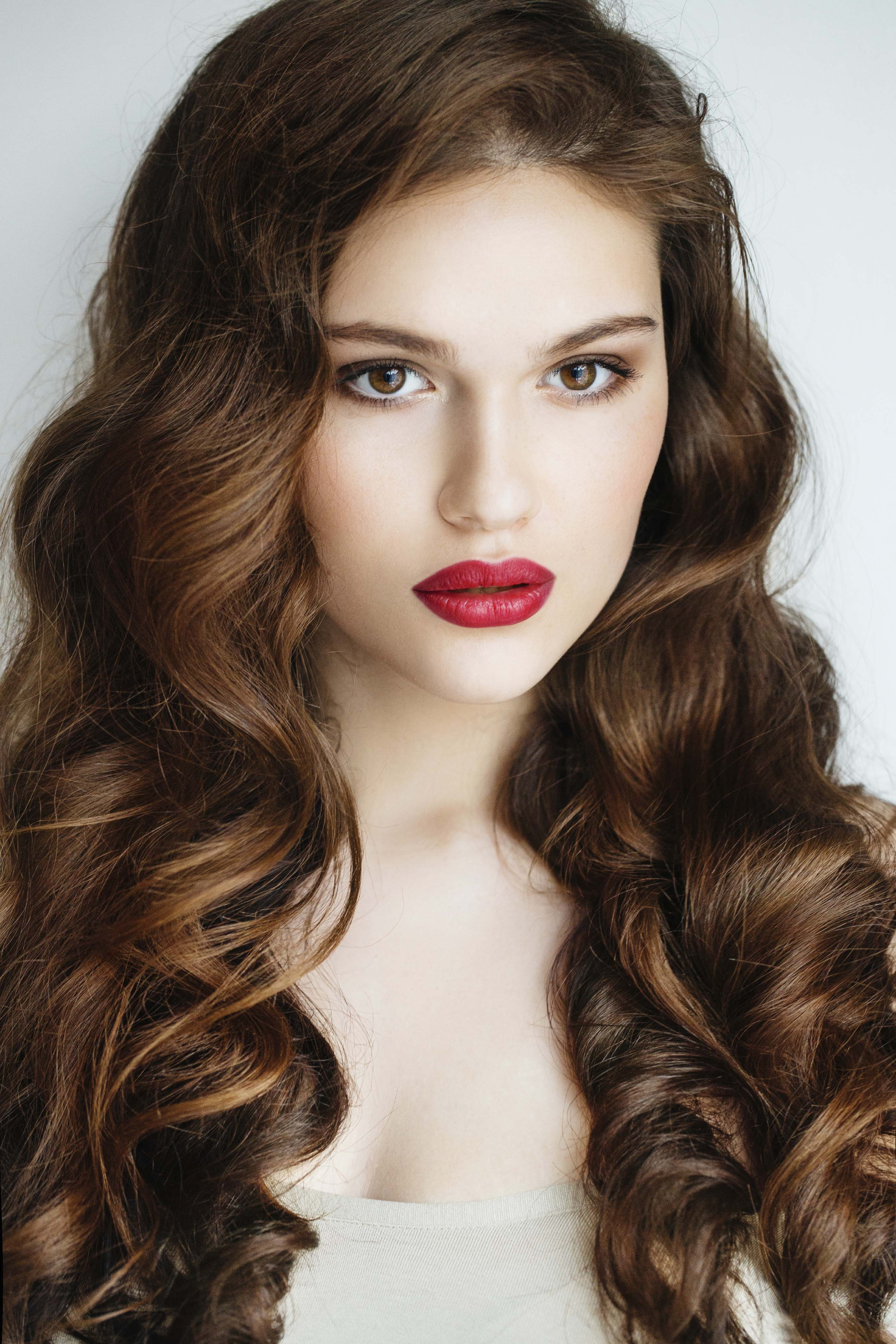 woman with long curly dark auburn red hair wearing red lipstick