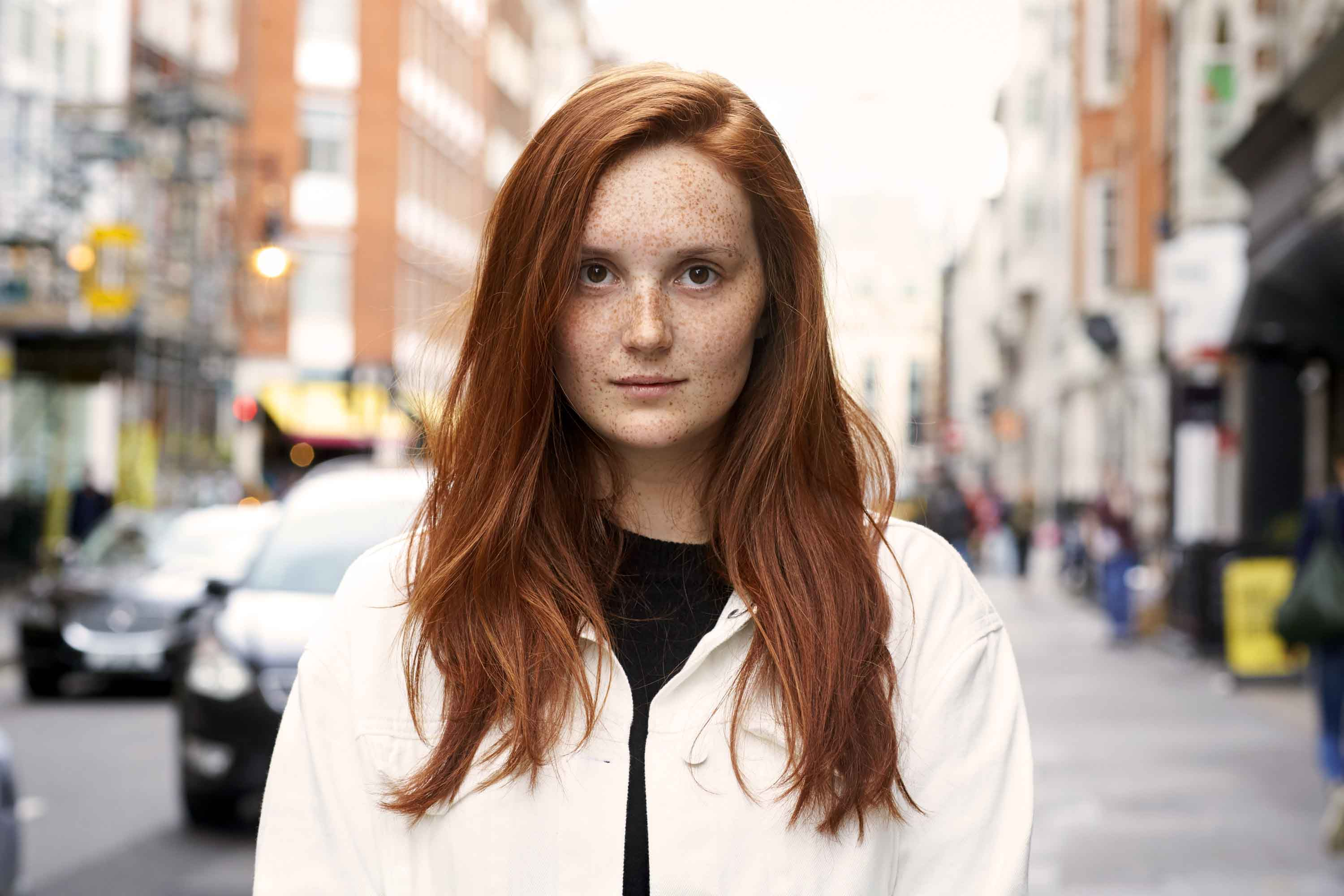 woman on the street with long pumpkin spice red hair with side parting