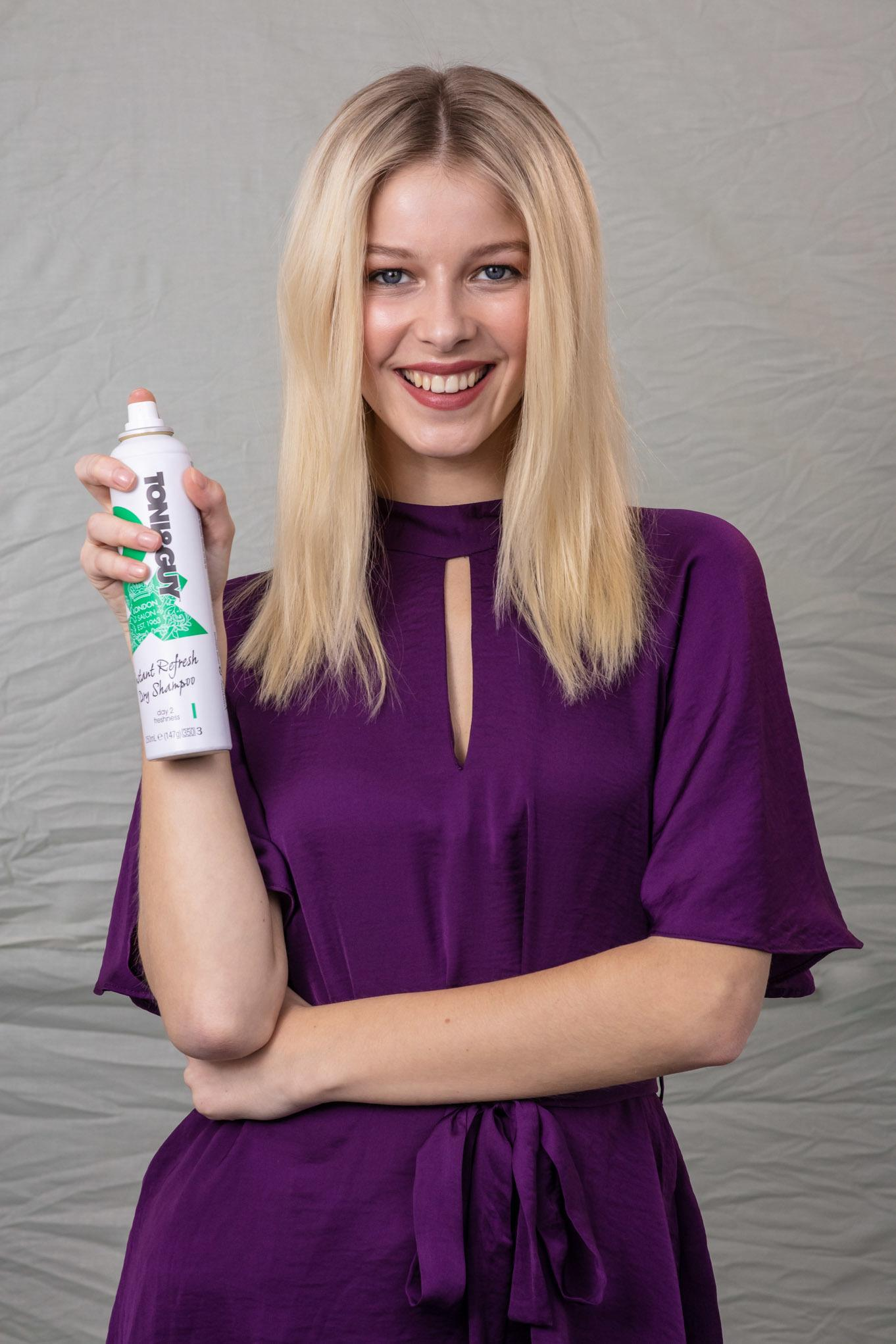 How to make hair look thicker: Blonde model with shoulder length hair, holding a can of dry shampoo, wearing a purple top