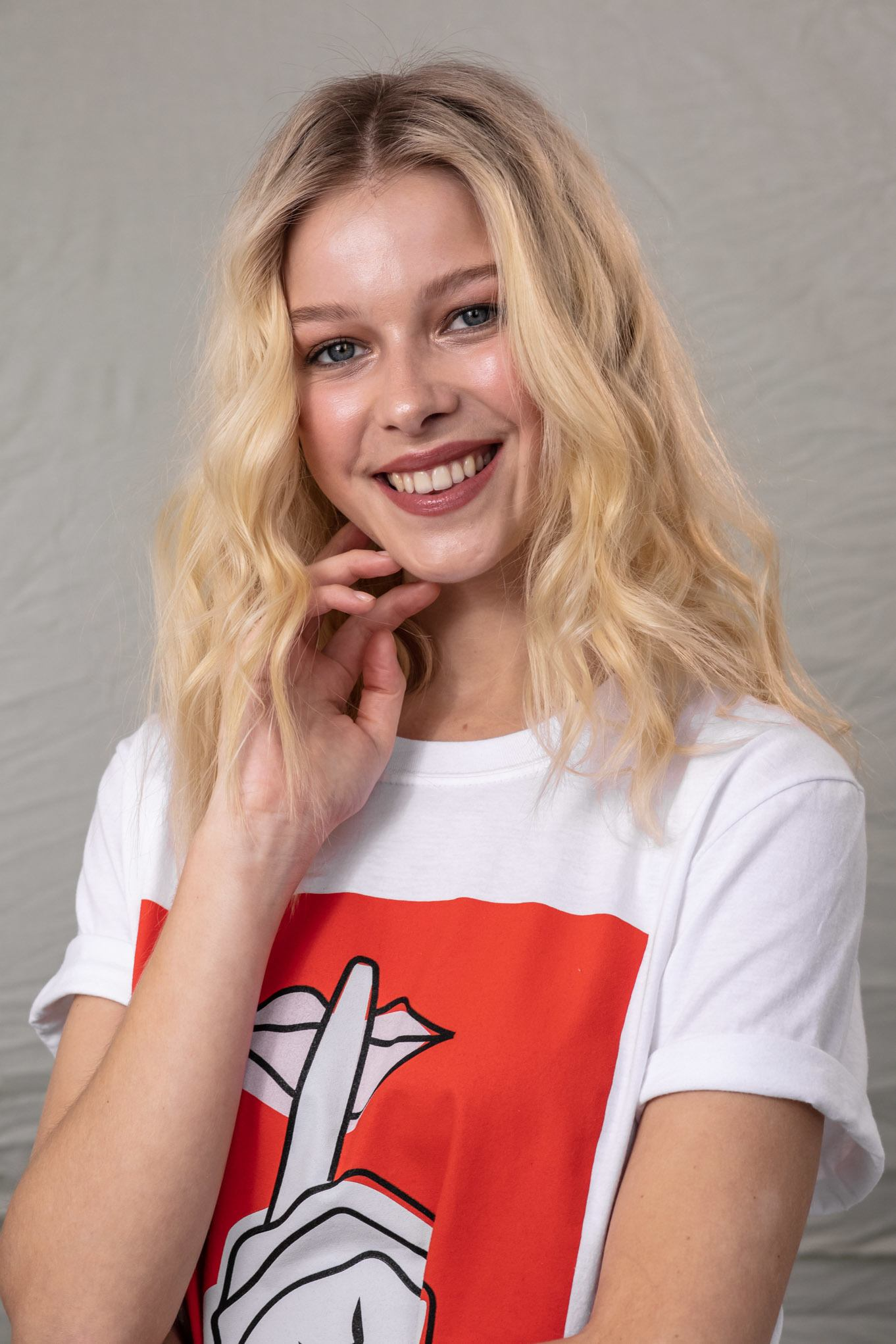 How to make hair look thicker: Blonde model with wavy shoulder-length hair, wearing a white t-shirt with red print