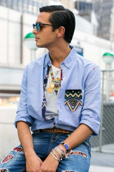man looking to the side wearing an all denim outfit with patterns on it and sunglasses with his dark brown hair styled into a classic comb over