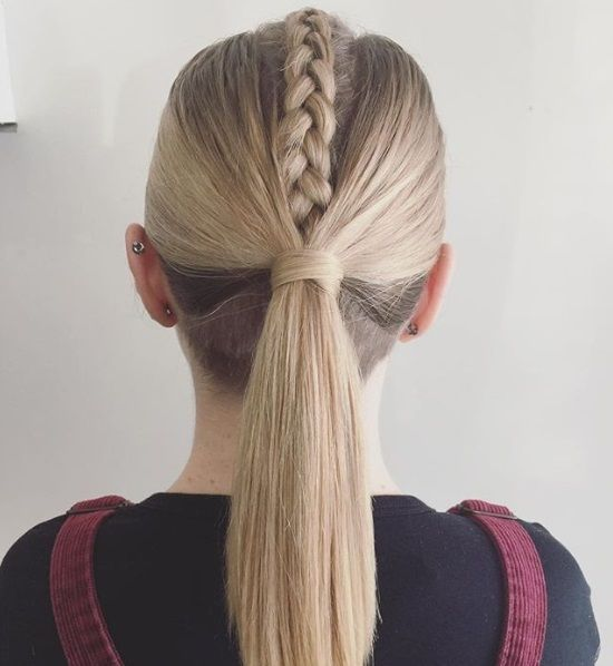 Back view of a woman with ash blonde straight hair in a middle Dutch braid and a wrapped ponytail