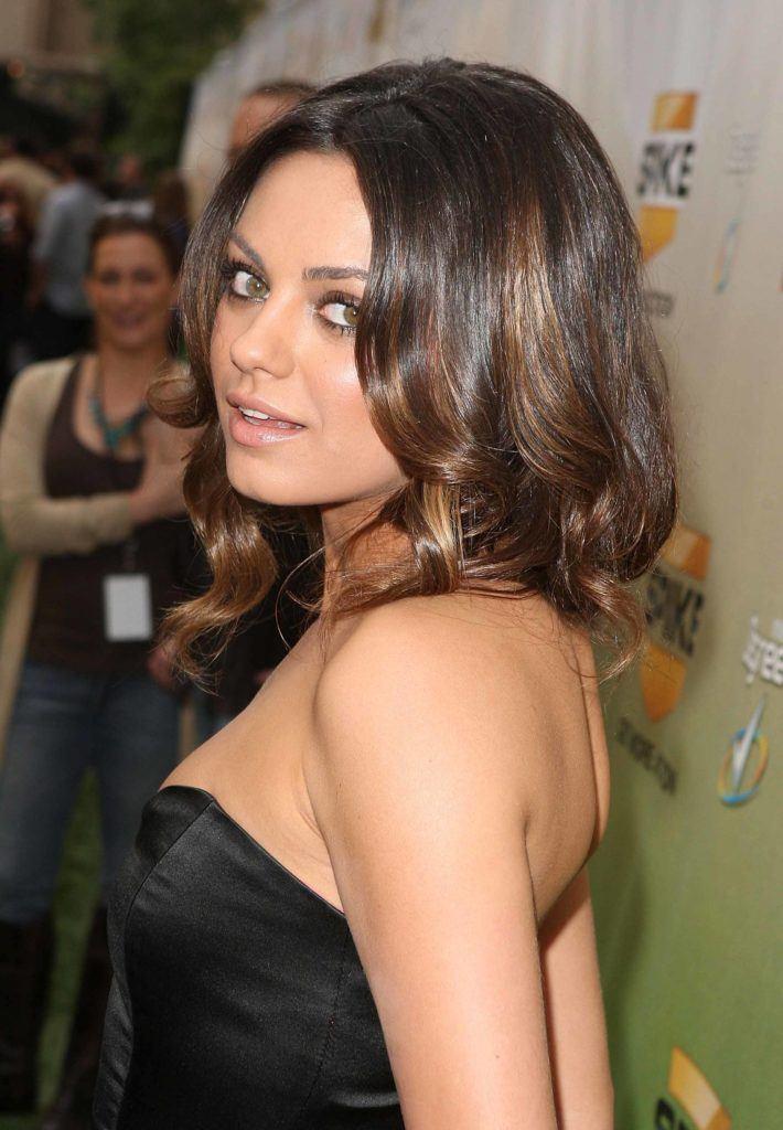 mila kunis with caramel balayage medium length curly hair wearing strapless black satin dress at awards show