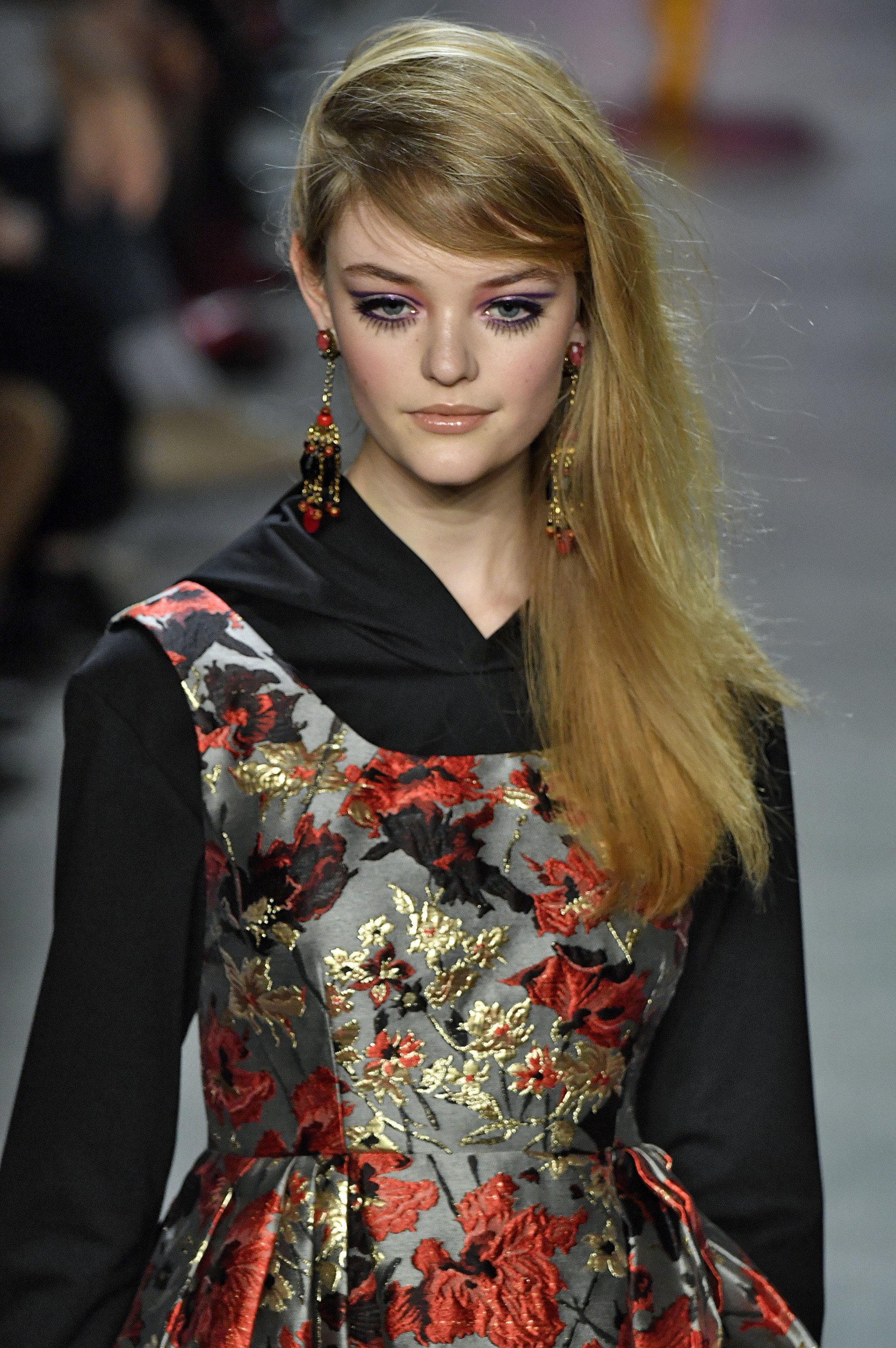 blonde model with long hair in deep side parting with sweeping fringe wearing dark floral pattern dress at runway show