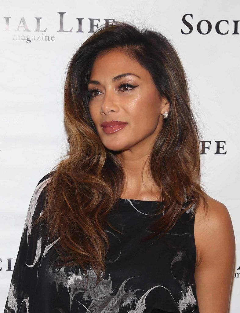 Nicole Scherzinger at industry event with long caramel balayage hair wearing one sleeve black patterned dress