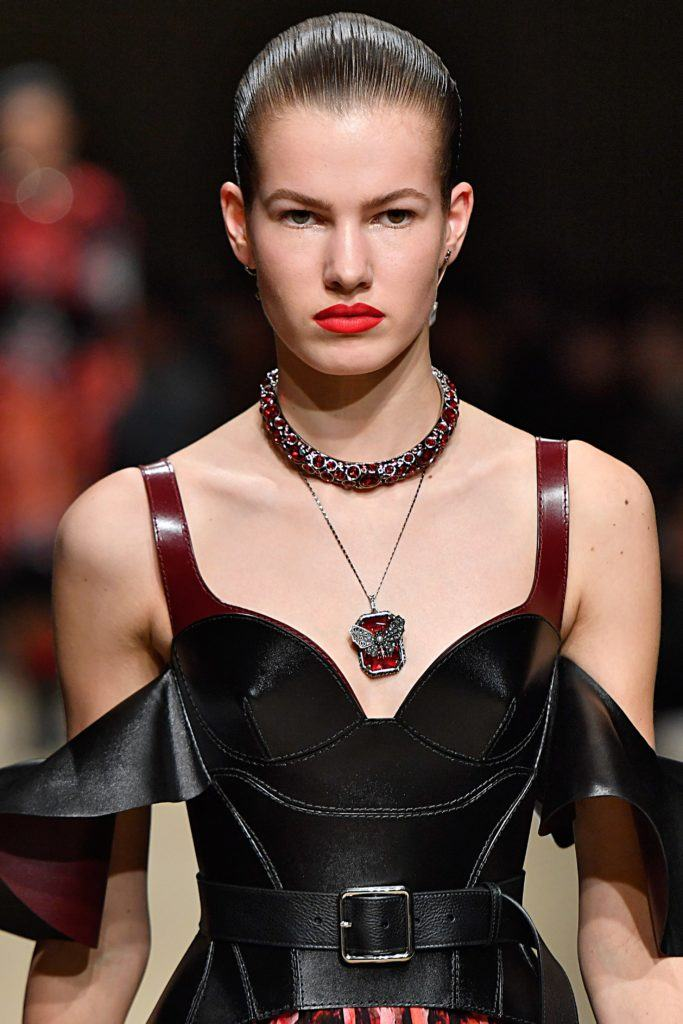 model on runway with brown hair smoothed back into wet-look updo wearing red lipstick and black off the shoulder dress