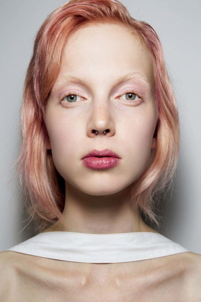 woman with rose gold bob-length hair in side-parting with tousled undone finish