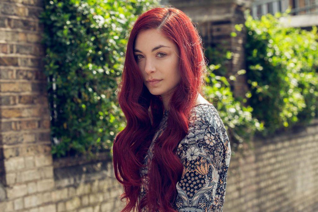 woman with long cherry brown red hair with side-parting and wavy finish wearing pattern top