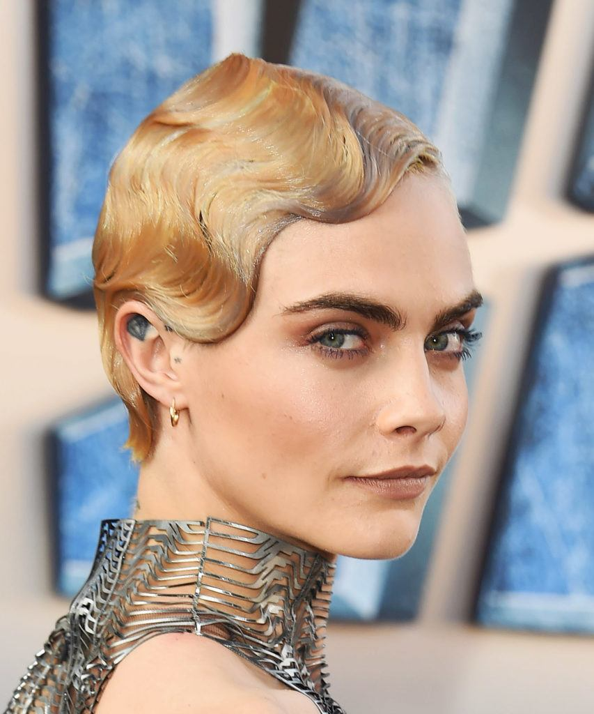 1920s hairstyles: front facing image of Cara Delevingne with short hair and finger waves on blonde short hair