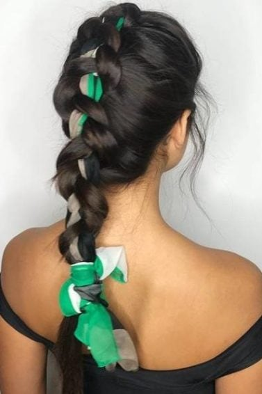 Dutch Braid Hairstyles: Woman with long dark brunette hair in a single large Dutch braid with a green print scarf woven through