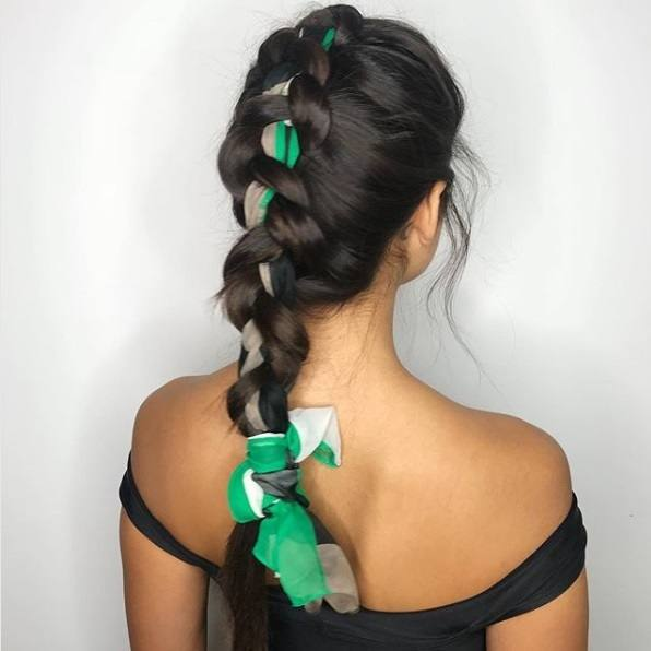Woman with long dark brunette hair in a single large Dutch braid with a green print scarf woven through