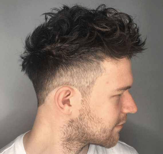 Men's haircuts for round faces: A man with dark cropped curly hair top and fade