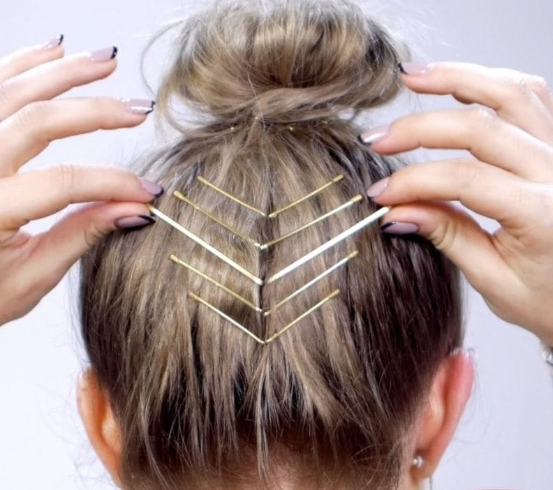 model with dark blonde hair in a top knot with chevron bobby pins
