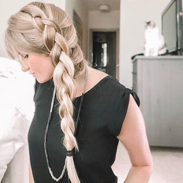 Blonde woman with long hair in a voluminous side Dutch braid