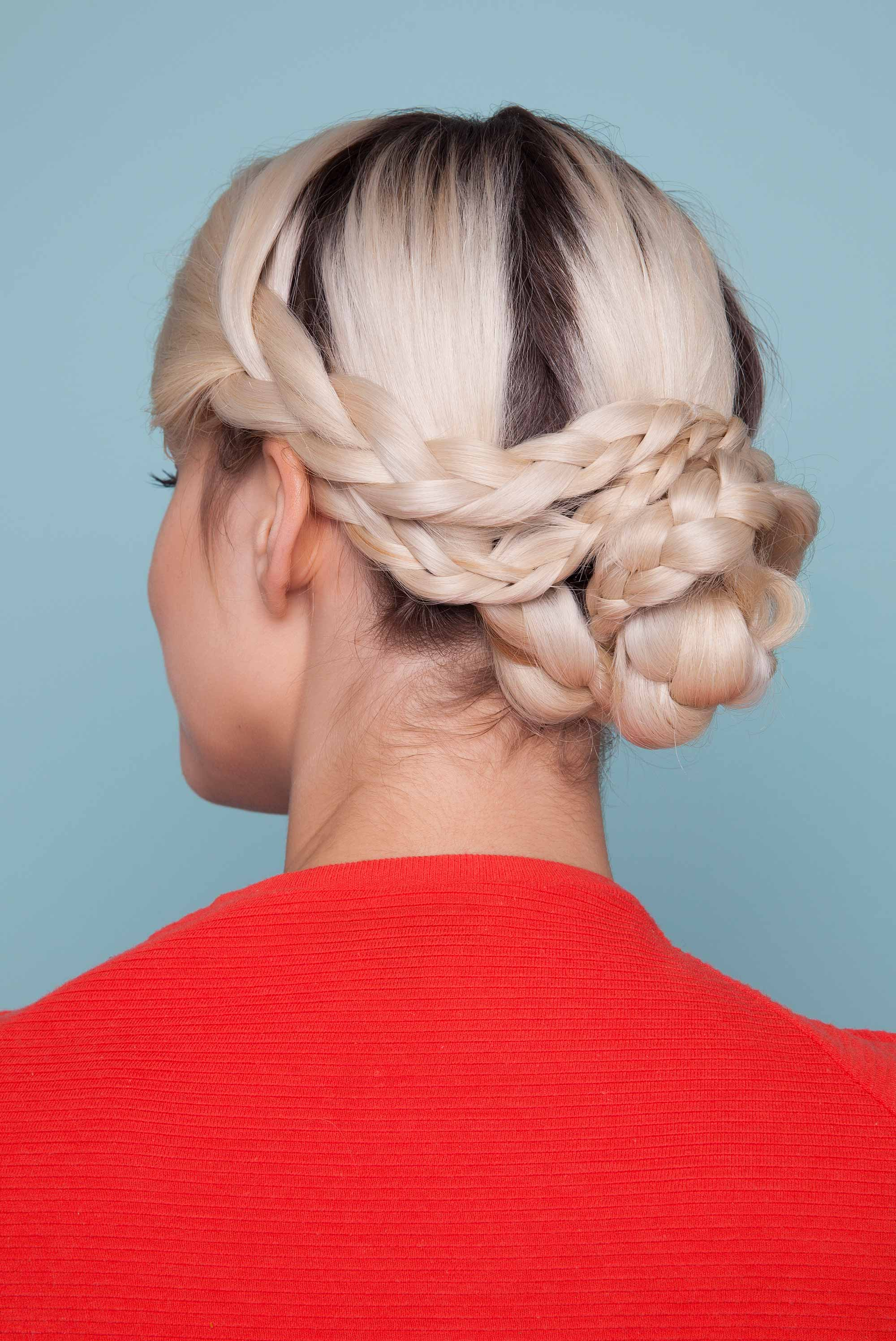 Snake braid hairstyles: Back view of blonde woman with hair styled in a snake braid bun updo.