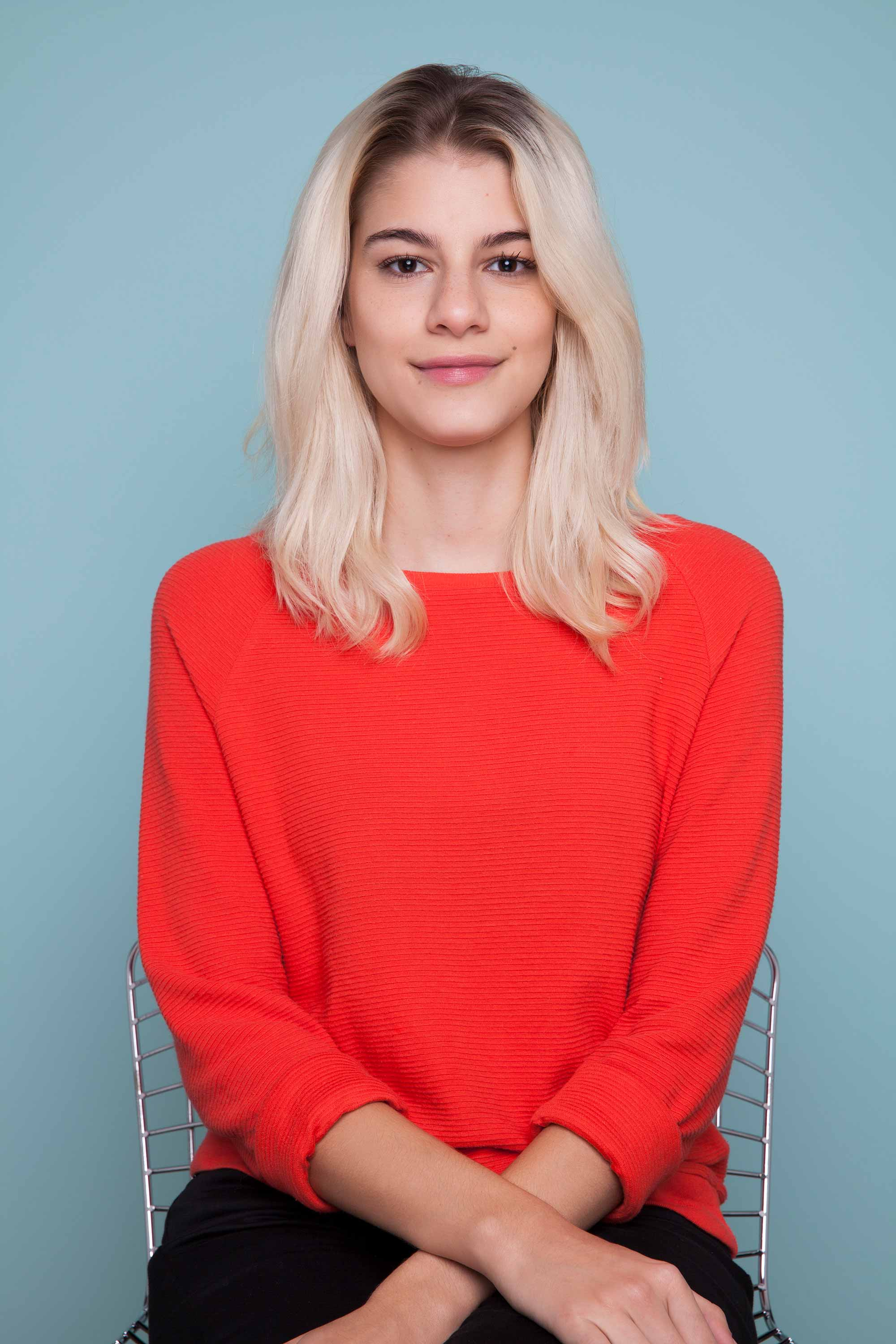snake braid hairstyles: Blonde woman with medium length hair sitting in studio with blue background wearing a red jumper.