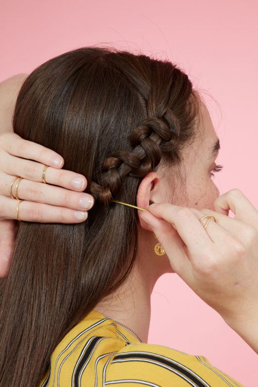 Snake braid hairstyles:Brunette model with long straight hair securing a snake braid behind her ear using bobby pins. Picture taken in a studio with pink background. Model is wearing a yellow striped dress.