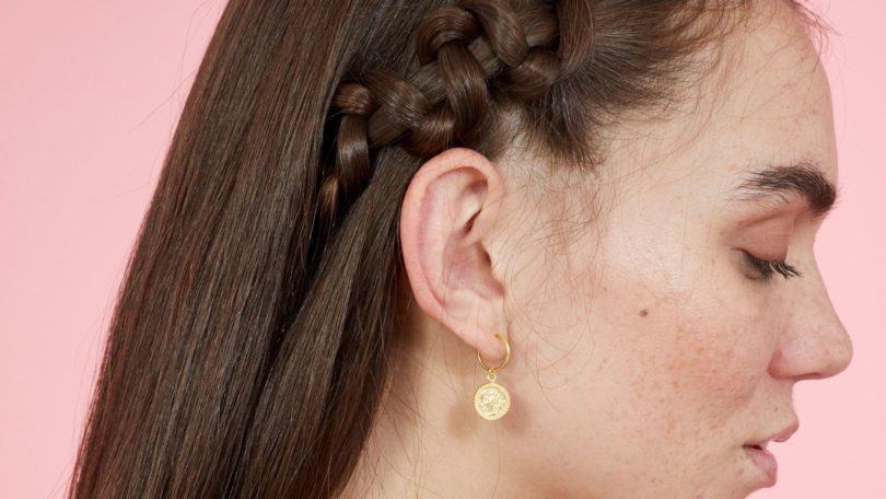Snake braid hairstyles: Side view of brunette woman with long straight hair styled with snake braid. Picture taken in a studio with pink background. Model is wearing a yellow striped dress.
