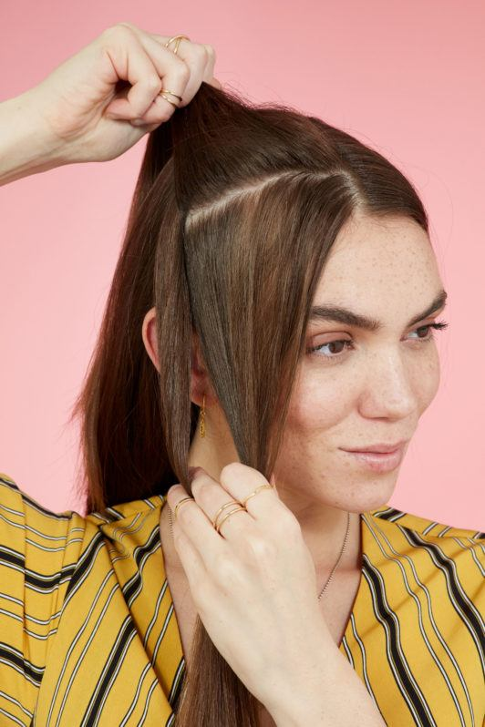 Snake braid hairstyles: Brunette model with long straight hair creating a parting from her crown to ear. Picture taken in a studio with pink background. Model is wearing a yellow striped dress.