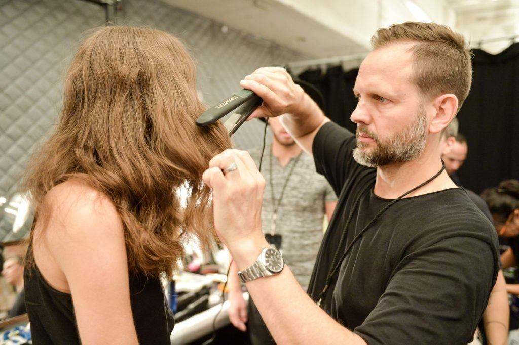 stylist Thomas Osborn backstage at the Jonathon Simkhai SS17 show styling a model's hair by