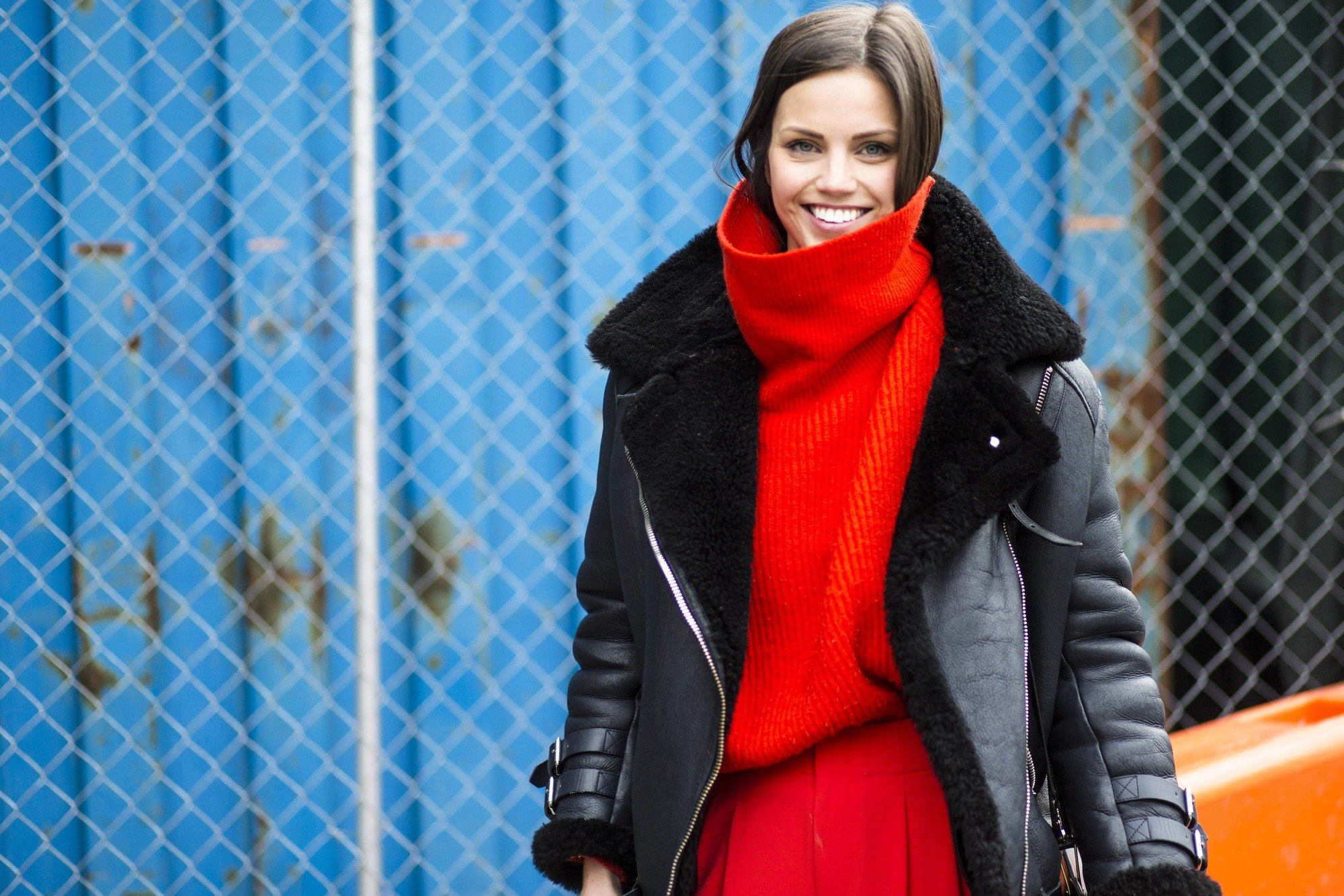 brunette nyfw street styler with her brunette straight hair tucked into an oversized red roll neck knit
