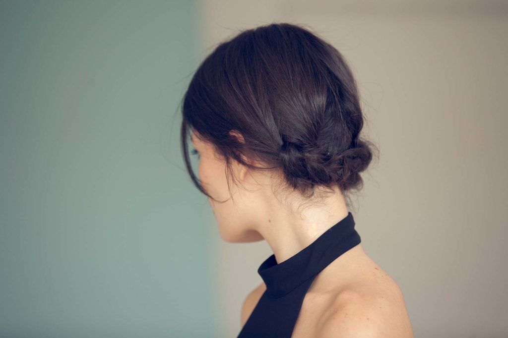 updos for short hair: back view of model with brown hair styled in a low twisted hairstyle
