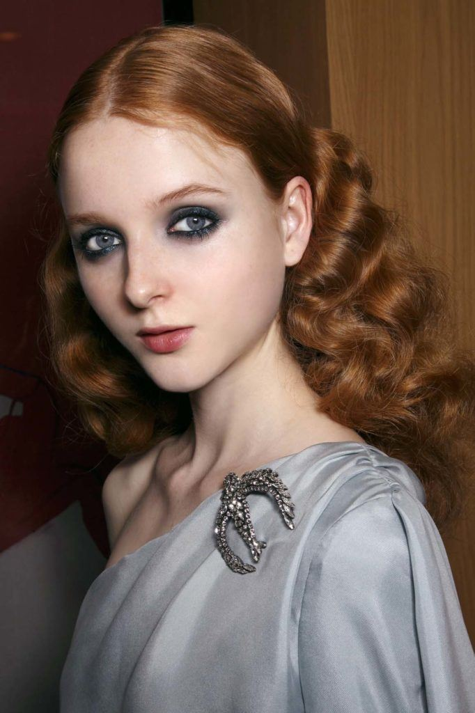 model with auburn curly medium-length red hair in centre parting