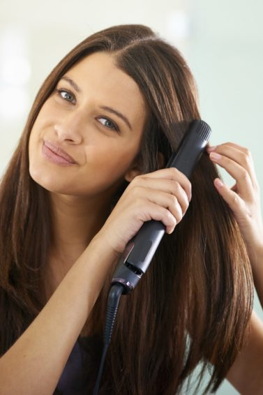 A dark haired woman straightening hair