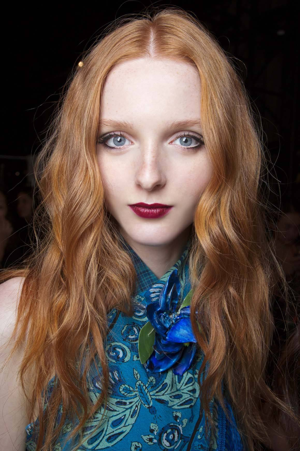 fair skinned model with long wavy ginger copper red hair wearing blue top and berry lipstick