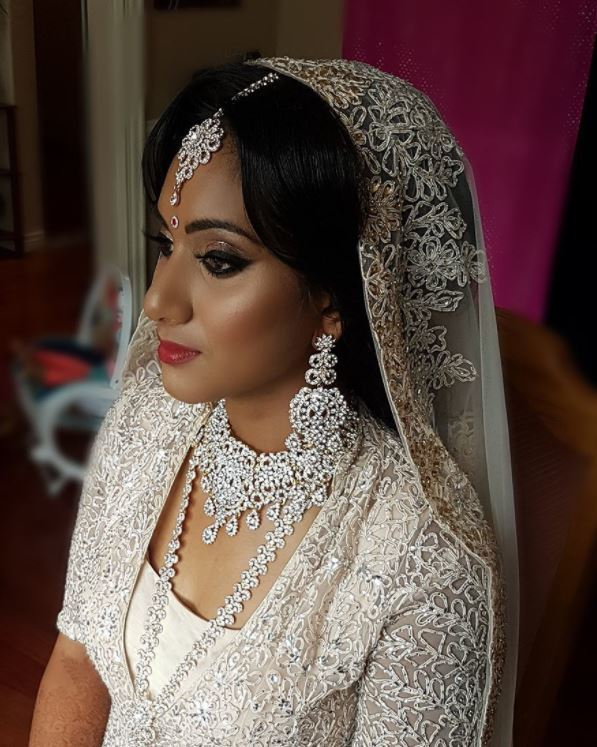 Indian wedding hairstyles: close up shot of woman with dark voluminous split bangs, wearing a veil and a white outfit with traditional Indian wedding jewellery
