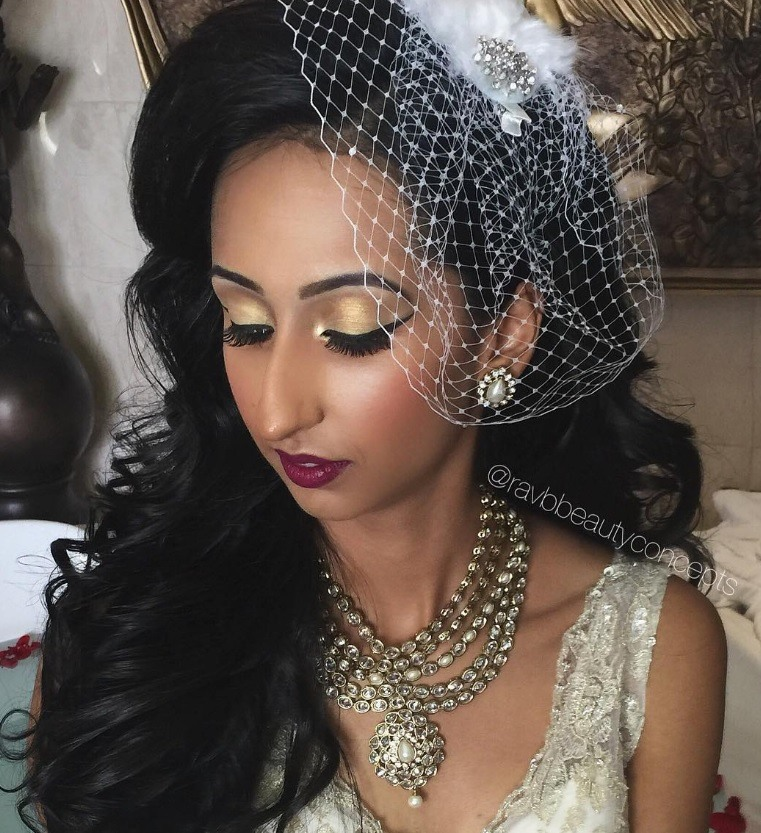 Indian wedding hairstyles: close up shot of woman with dark, long curly hair swept to the side with vintage netting fascinator adorned over it