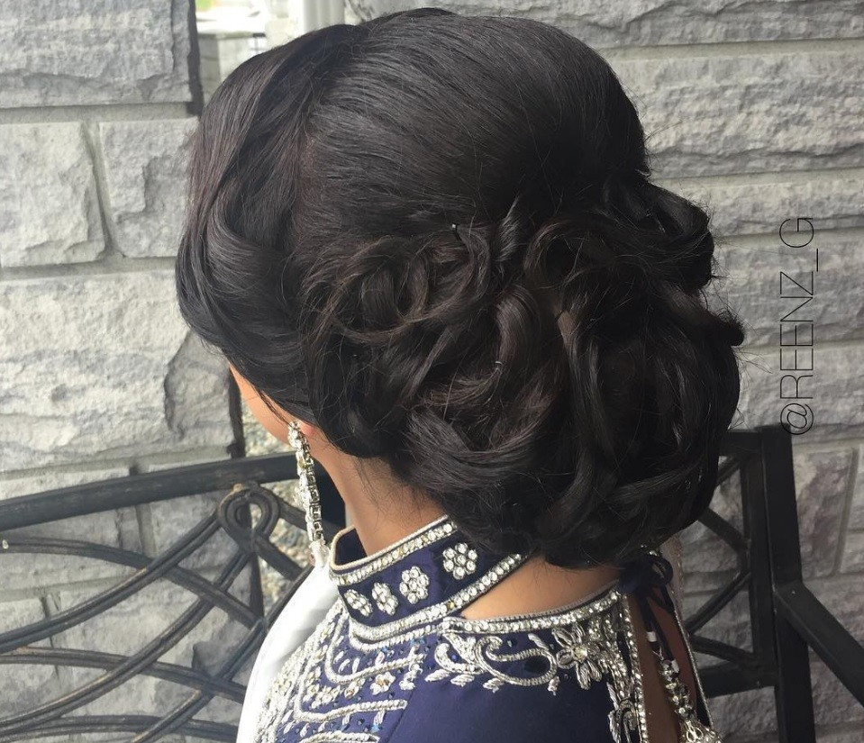 Indian wedding hairstyles: close up shot of woman with black hair wrapped into low intricate bun, wearing Indian wedding outfit and posing in a salon