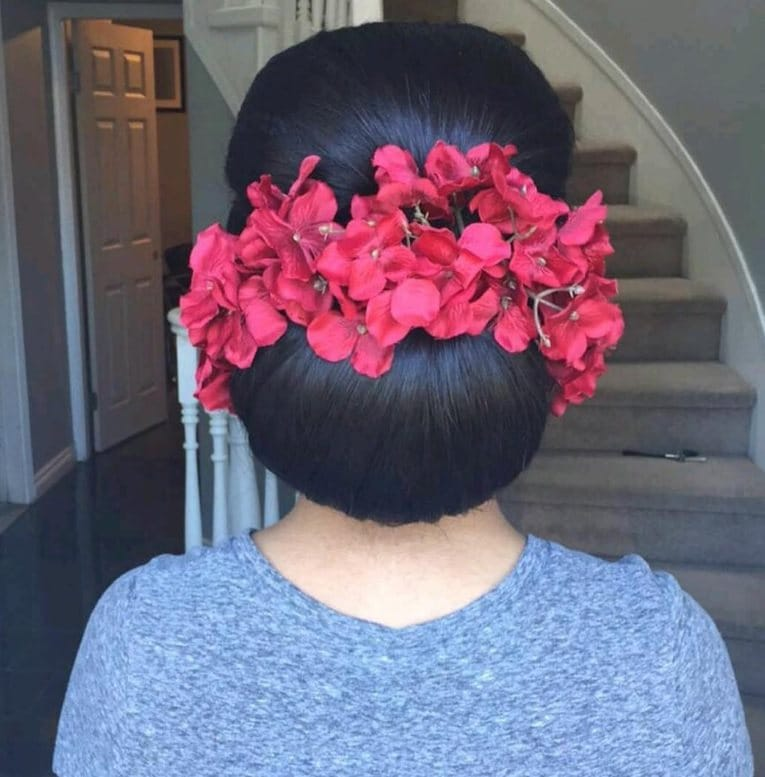 Indian wedding hairstyles: close up shot of a bride with dark hair styled into a smooth and elegant chignon, adorned with red floral accessories