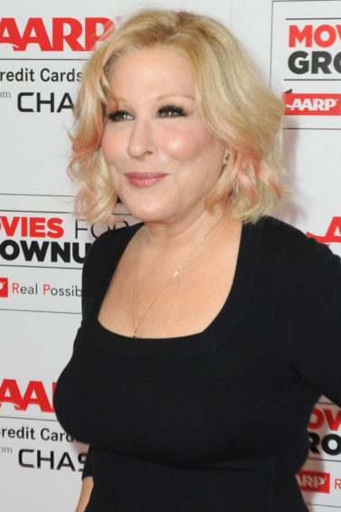 Bette Midler on the red carpet wearing black top and navy spriped trousers with her hair worn in a blonde bob cut with pink highlights