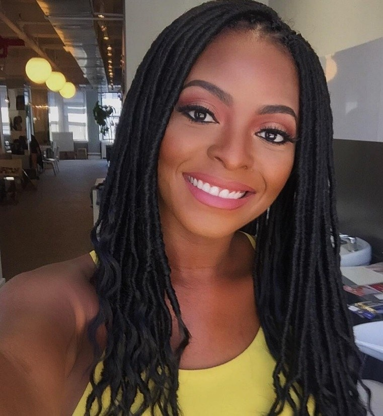 Black History Month hair: Close up shot of a woman with dark brown long faux locs, wearing a yellow top and posing in a bathroom