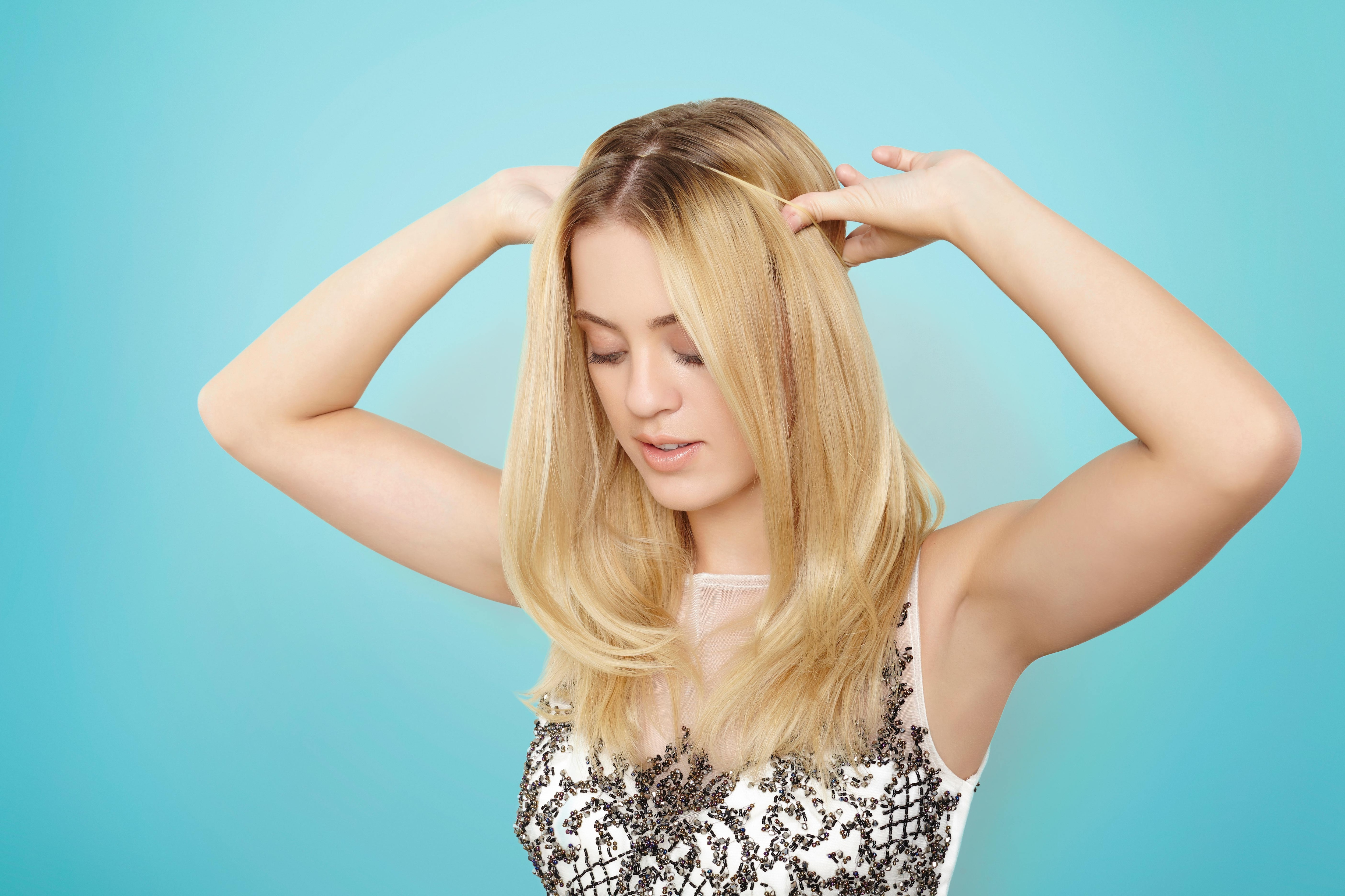 blonde model with shoulder length straight hair putting an elastic hairband around her hair