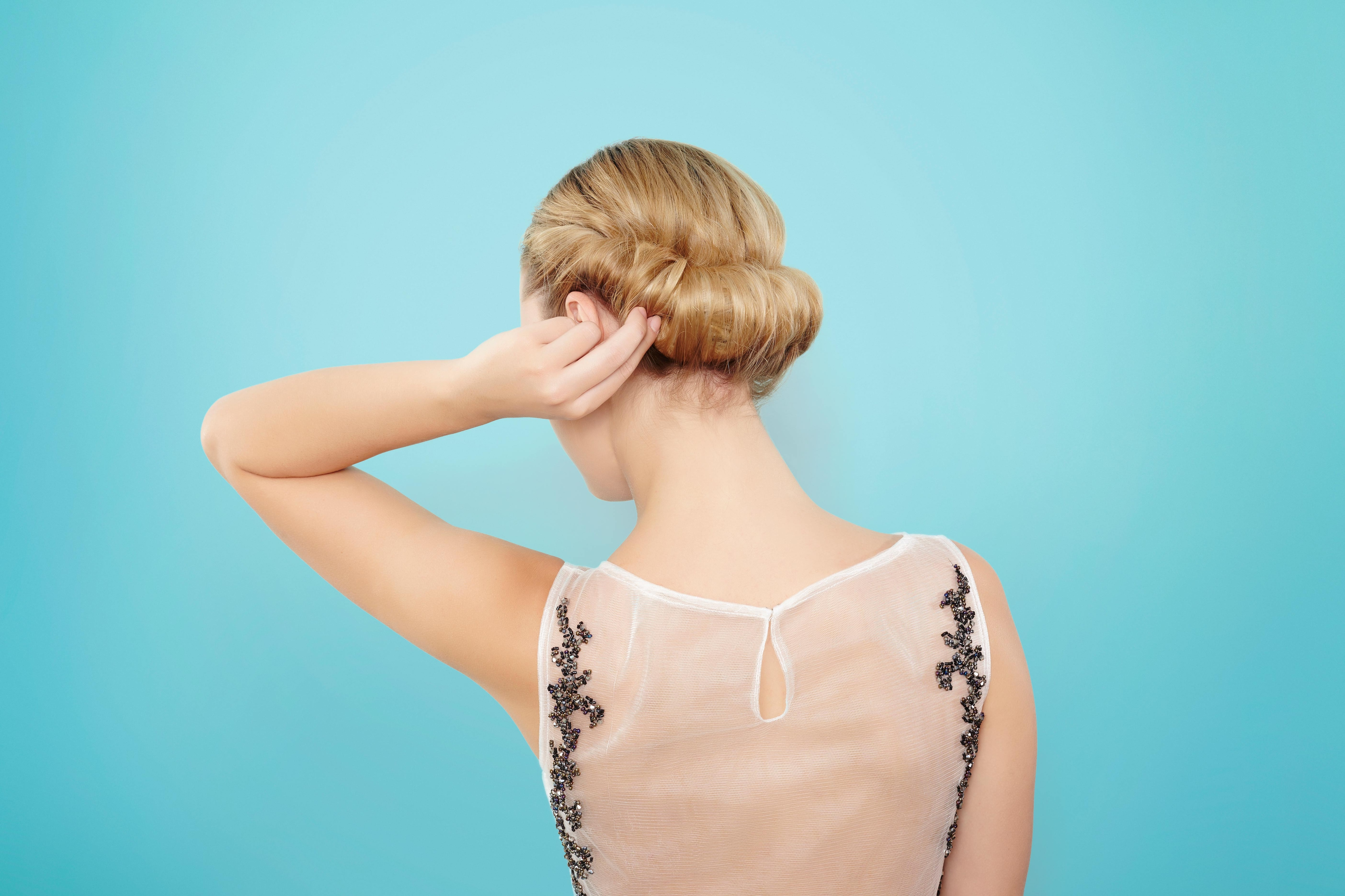 back view of a blonde model twisting her hair into a croissant chignon updo