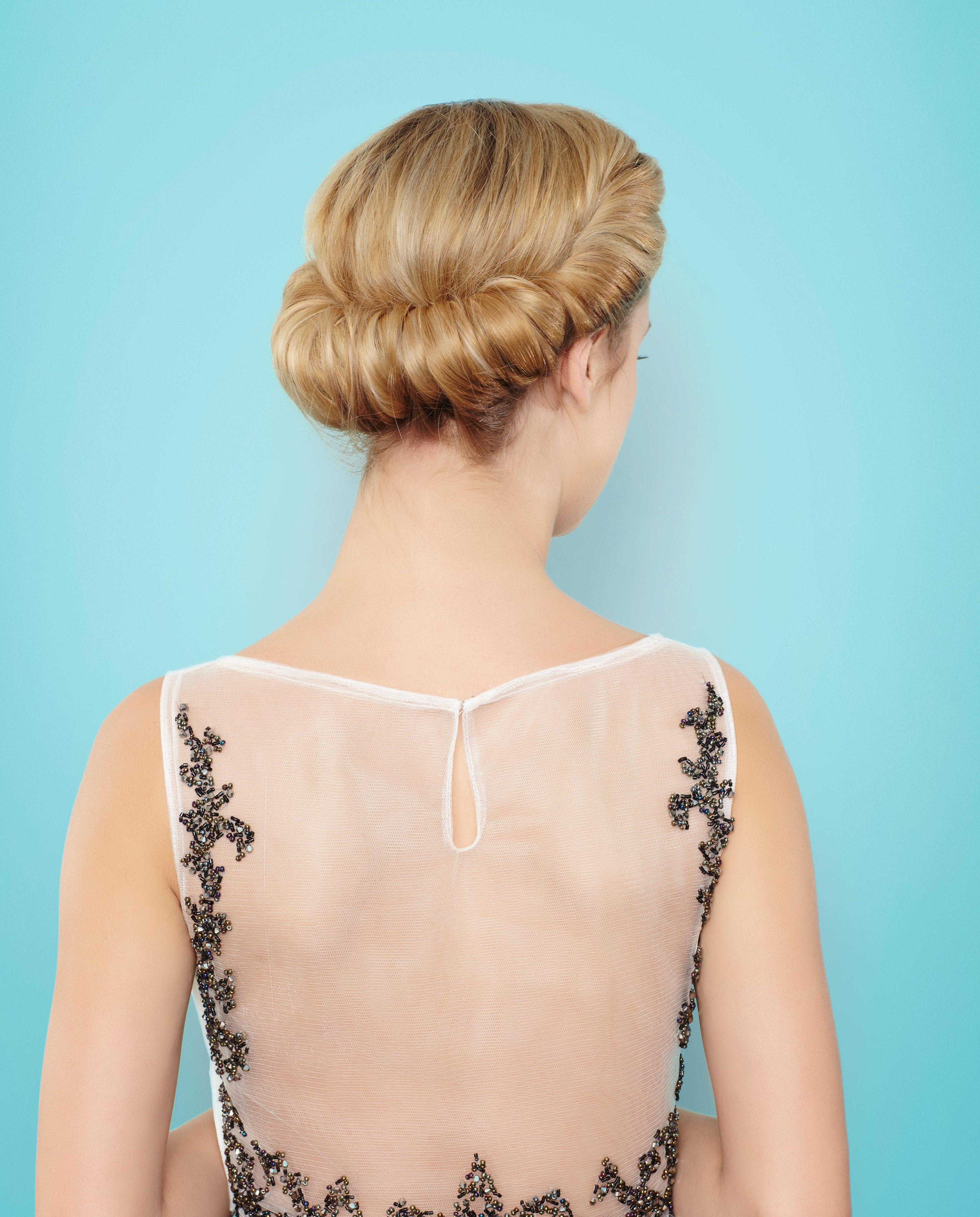 back view final look at blonde model with her hair in a twisted croissant chignon updo
